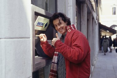 Young man using ATM machine on street, portrait, waist up