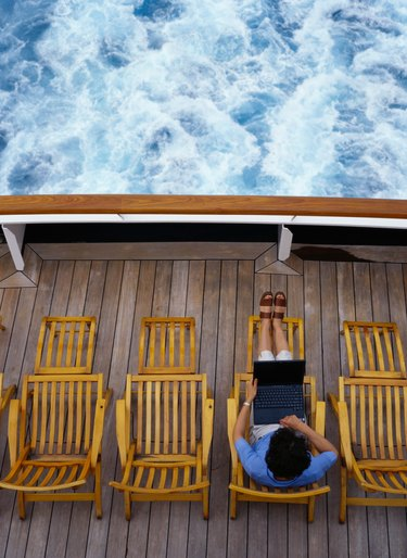 Woman Typing on a Laptop on a Cruise Ship Deck