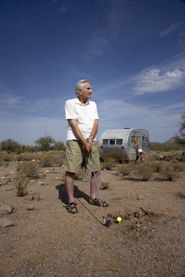 Man playing golf in desert and teenage girl (14-15)  leaning on trailer in background