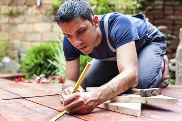 Young man building a backyard deck