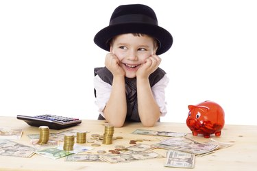 Happy boy at the table with money
