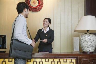 Businessman at Reception Desk of Hotel