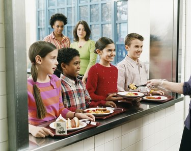 Four Schoolboys and Schoolgirls Looking at Person Serving Food on a Plate