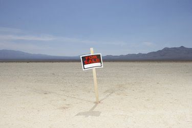 'For sale' sign in dry lake bed