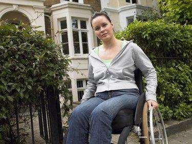 Woman sitting in wheelchair outside house, portrait