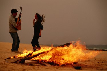 Young couple dancing by campfire at beach