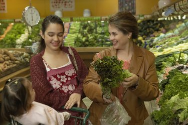Mid adult woman and her two daughters buying vegetables in a supermarket