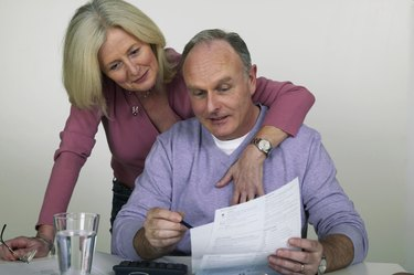 Mature woman with arm around mature man at desk pointing to bill