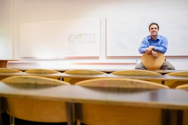 Male teacher sitting on chair in lecture hall