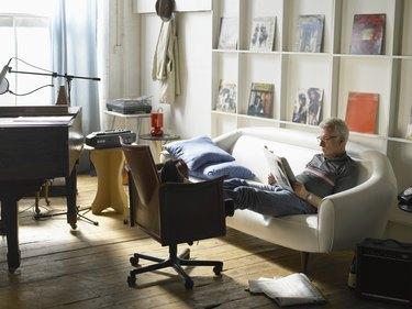 Mature man sitting on sofa, reading newspaper