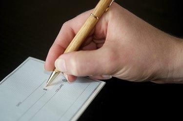 Woman's hand writing a check