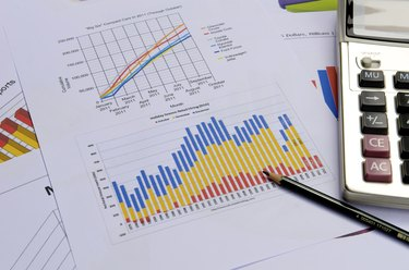 business charts and graphs with pen and calculator