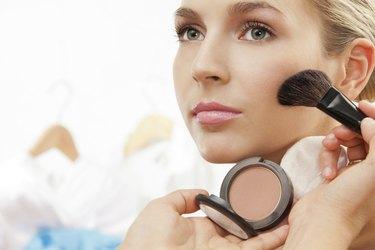 Using brush to apply blush on cheeks