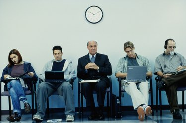 Business executives sitting in a row operating laptops
