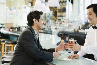 Male bartender serving man drink at bar