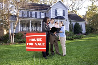 A real estate agent talks to a young family about the suburban home for sale