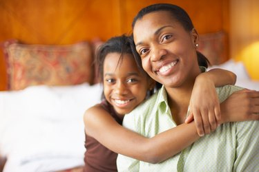 Portrait of mother with daughter in hotel room