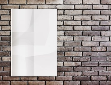 Template- White crumpled  Poster on grunge brick wall and leave