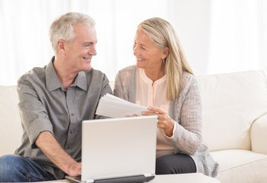 Couple With Laptop Paying Bills Online At Home