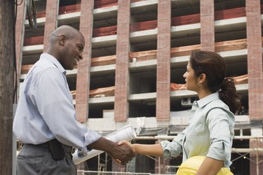 Architects shaking hands at construction site