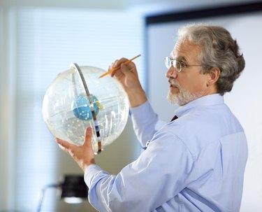Professor holding astronomical globe
