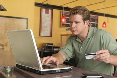 Close-up of a young man using a laptop and holding a credit card for online shopping