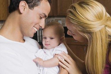 Hispanic parents smiling at baby