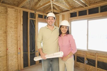 Couple in hard hats with blueprints on construction site