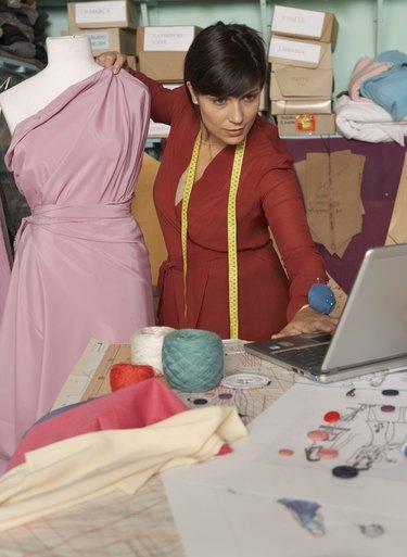 Female fashion designer using laptop in studio