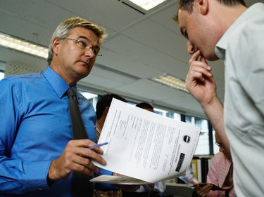 Two businessmen in office, one holding paperwork