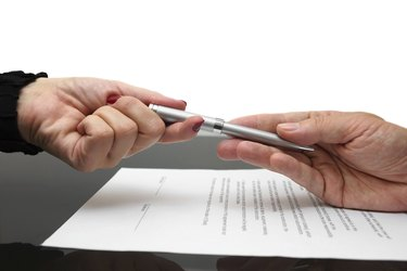 businessman giving pen to businesswoman for signing contract or document