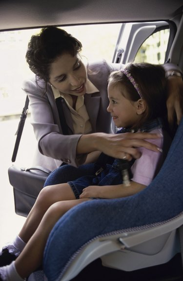 Mother placing her daughter in a car seat