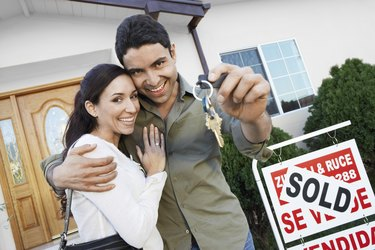 Happy Homeowners with <Sold> Sign