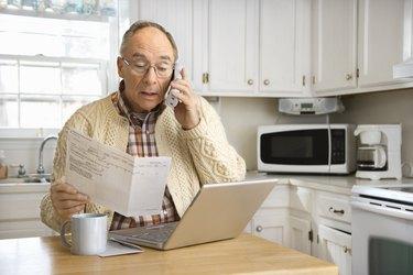 Senior man using computer and cordless phone
