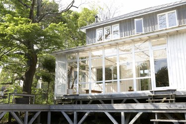 Conservatory of wood-panelled home with wooden deck