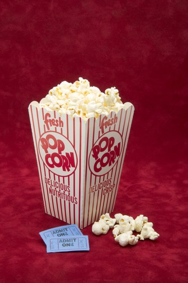 Box of movie popcorn and admission tickets