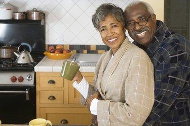 Senior African couple hugging in kitchen
