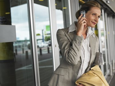 Businesswoman using mobile phone outdoors, smiling