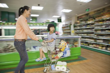 Mother and daughter holding apple, shopping for groceries, Beijing