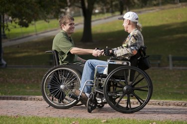 Two veterans shaking hands in wheelchairs