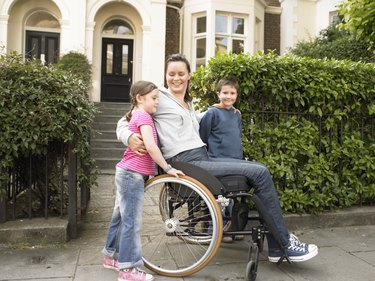 Mother in wheelchair outside house, arms around children (7-9) smiling