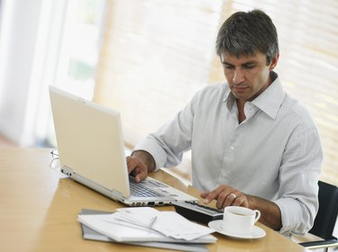 Man using laptop and calculator at desk