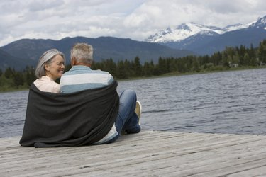 Mature couple sitting on pier wrapped with blanked, mountain range in background