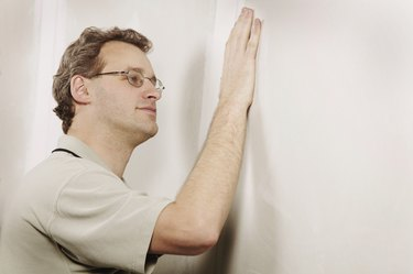 Man checking the smoothness of a wall