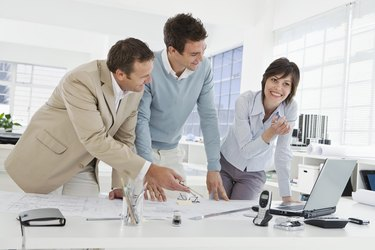 Architects with blueprints and laptop