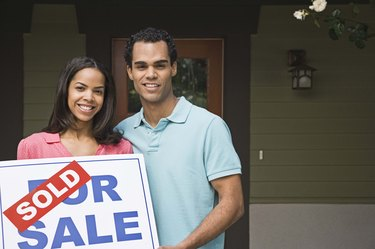 Couple with house and sold sign