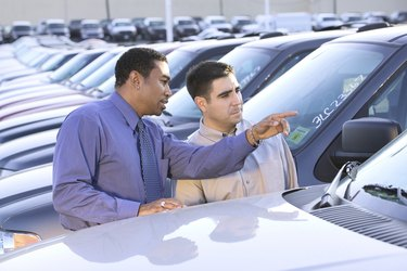 A salesman points out features of a new car to an interested customer