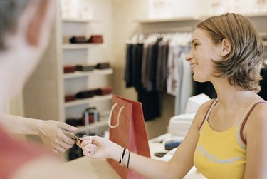 Teenage girl paying in clothing store