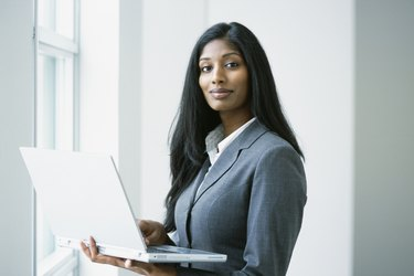 Indian businesswoman holding laptop