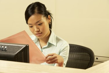 Woman reading paperwork at desk, head and shoulders